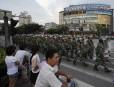 Des résidants regardent les policiers anti-émeutes défilés dans les rues.... | 15 juin 2011