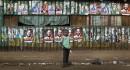 Un garçon se tient devant un mur tapissé d'affiches électorales,... | 7 mars 2013