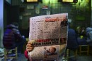Un homme consulte un journal qui dépeint la chancelière allemande,... | 17 mars 2017