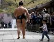 Un jeune garçon suit un lutteur de sumo, alors qu'il... | 17 avril 2017