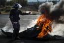 Un policier sud-africain tente d'éteindre un feu de pneus allumé... | 11 mai 2017