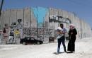 Une famille palestinienne passe devant un graffiti sur le mur... | 15 mai 2017