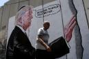 Un homme marche devant un graffiti mettant en vedette le... | 4 août 2017