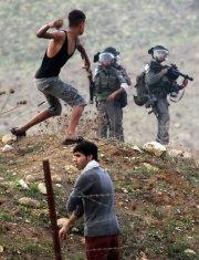 Un jeune palestinien lance une roche vers des... (Photo: Reuters) - image 2.0
