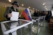 Une femme dépose son bulletin de vote en... (PHOTO SERGEI KARPUKHIN, REUTERS) - image 1.0