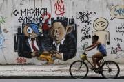 Une Brésilienne passe en vélo devant un graffiti... (Photo Sergio Moraes, archives Reuters) - image 2.0