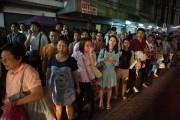Des Thaïlandais attendent des taxis, pressés de rentrer... (Photo Nicolas Asfourni, AFP) - image 2.0