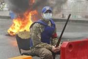 Un activiste est assis près de pneus qui... (PHOTO VALENTYN OGIRENKO, REUTERS) - image 2.0