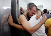 Des Palestiniens pleurent la mort de leurs proches... (Photo: Reuters) - image 2.0