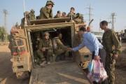 Un civil israélien apporte des cadeaux à des... (Photo: AFP) - image 3.0
