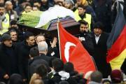 Après les funérailles, tenues autour de deux drapeaux... (PHOTO KAI PFAFFENBACH, REUTERS) - image 2.0