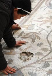 Un homme regardeune mosaïque qui a été légèrement... (PHOTO HASSAN AMMAR, AFP) - image 1.0