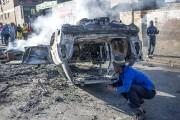 Des gens examinent la carcasse d'une voiture incendiée... (PHOTO MUJAHID SAFODIEN, AFP) - image 4.0