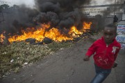 Un garçon passe devant des pneus en feu,... (PHOTO MUJAHID SAFODIEN, ARCHIVES AFP) - image 2.0