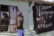 Un homme remplace la vitre cassée d'une taverne... (PHOTO SCHALK VAN ZUYDAM, ARCHIVES AP) - image 3.0