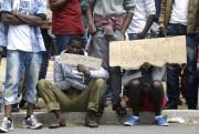 Plusieurs migrants portent des pancartes demandant de pouvoir... (Photo Lionel Cironneau, AFP) - image 1.0