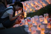 Dimanche, la population a observé une minute de... (Photo Eugene Hoshiko, AP) - image 1.0