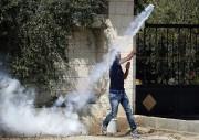 Un Palestinien relance en direction des soldats israéliens... (PHOTO NASSER SHIYOUKHI, AP) - image 2.1