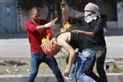 Des militants palestiniens tentent d'éteindre les vêtements en... (PHOTO MUSSA QAWASMA, REUTERS) - image 3.0