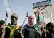 Des étudiants palestiniens masqués brandissent des hachettes alors... (PHOTO SAID KHATIB, AFP) - image 1.0