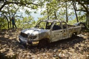 Une camionnette incendiée est vue sur le terrain... (PHOTO RONALDO SCHEMIDT, AFP) - image 3.0