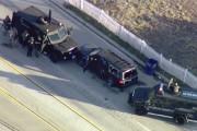 Des policiers sont massés derrière leurs véhicules près... (AP, KTTV) - image 1.0