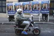 Un motocycliste passe devant une affiche du Front... (AP, Claude Paris) - image 19.0