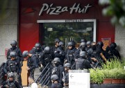 Des policiers des forces spéciales sont regroupés devant... (PHOTO BEAWIHARTA/REUTERS) - image 4.0