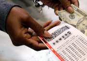 A clerk hands over a Powerball ticket for... (Photo Tony Dejak, associated press) - image 1.0