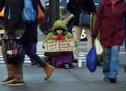 A homeless woman sits on 5th Avenue at... - image 1.0