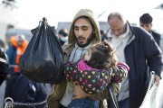 Un réfugié syrien transporte un enfant dans ses... (PHOTO PETROS GIANNAKOURIS, AP) - image 3.0