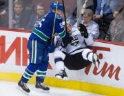 Vancouver Canucks' Alex Biega, left, checks Los Angeles... - image 1.0