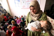 A displaced woman carries her child in a... - image 1.0