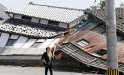 Une femme passe devant une maison détruite par... (PHOTO NAOYA OSATO, KYODO MEWS/AP) - image 4.0