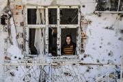 Une femme regarde par la fenêtre de sa... (PHOTO ILYAS AKENGIN, ARCHIVES AFP) - image 1.0