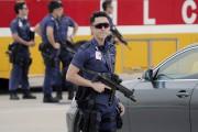 Des policiers lourdement armés montent la garde à... (PHOTO KIN CHEUNG, AP) - image 1.0