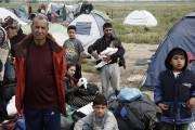 Des migrants et réfugiés attendent de monter à... (PHOTO YANNIS KOLESIDIS, ANA-MPA/AP) - image 1.0