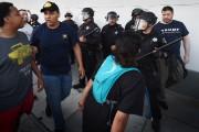Les policiers anti-émeute protègent ce partisan arborant fièrement... (PHOTO Mark Ralston, AFP) - image 2.0