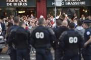 Des policiers gardent un oeil sur un groupe... (AFP, Philippe Huguen) - image 4.0