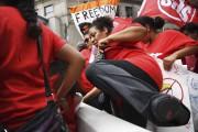 Des manifestants anti-Donald Trump sautent par-dessus une barrière... (AFP, Jim Watson) - image 4.0