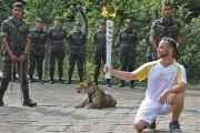 Un athlète tient la torche olympique devant un... (Archives AFP) - image 1.0