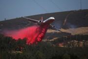 Un avion bombardier d'eau arrose un secteur duClayton... (REUTERS) - image 2.0