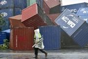 Un homme passe devant des conteneurs renversés par... (PHOTO SAM YEH, AFP) - image 1.0