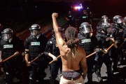 Un manifestant se tient le poing levé devant... (AP) - image 2.0