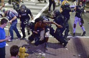 Des policiers arrêtent un manifestant, mercredi soir, à... (AP, Jeff Siner) - image 2.0