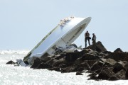Des enquêteurs examinent l'épave du bateau dans lequel... (AP) - image 1.0