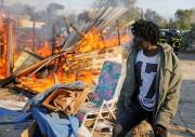Un migrant passe devant un abri en flammes,... (photo Pascal Rossignol, REUTERS) - image 3.0