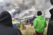 Des migrants observent la fumée s'élever au-dessus de... (AFP, Philippe Huguen) - image 2.0