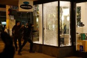 Un homme casse une vitrine lors d'une manifestation... (Photo William Gagan, REUTERS) - image 7.0