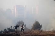 Des habitants tâchaient de contenir les flammes avec... (AFP) - image 2.0